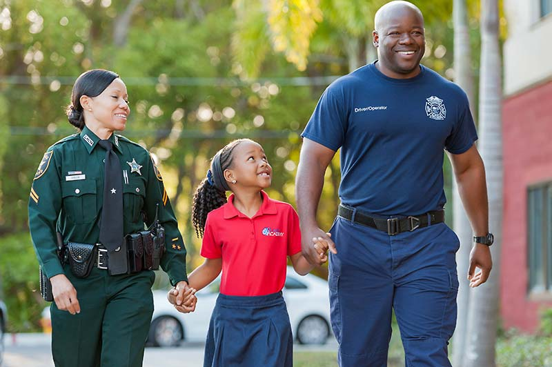 Girl student and police officer hold hands and smile as they walk to school