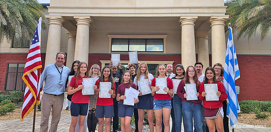 Plato Academy students pose holding their certificates.